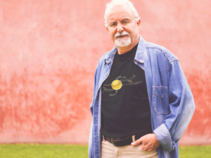 Older white male wearing a Bitcoin custom branded promotional clothing shirt.