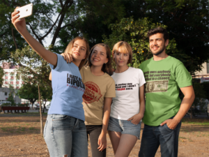 Four friends taking a selfie with an iPhone wearing promotional clothing.